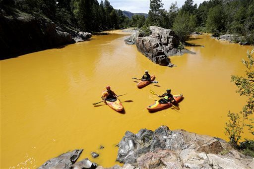 FILE - In this Thursday, Aug. 6, 2015 file photo, people kayak in the Animas River near Durango, Colo., in water colored yellow from a mine waste spill. A crew supervised by the U.S. Environmental Protection Agency has been blamed for causing the spill while attempting to clean up the area near the abandoned Gold King Mine. Tribal officials with the Navajo Nation declared an emergency on Monday, Aug. 10, as the massive plume of contaminated wastewater flowed down the San Juan River toward Lake Powell in Utah, which supplies much of the water to the Southwest. (Jerry McBride/The Durango Herald via AP, FILE) MANDATORY CREDIT