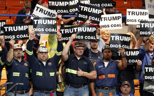 A group of coal miners wave signs for Republican presidential candidate Donald Trump as they wait for a rally in Charleston, W.Va., Thursday, May 5, 2016. (AP Photo/Steve Helber)