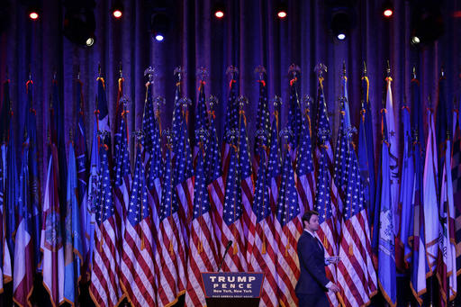 A man walks across the stage during preparations for Republican presidential candidate Donald Trump's election night rally, Tuesday, Nov. 8, 2016, in New York. (AP Photo/John Locher)