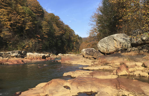 In this Nov. 1, 2016 photo, the Cheat River runs green and slate gray and low among brown boulders in the whitewater canyon. It was recently bought by the state and environmentalists to protect the once badly polluted river, its tributaries and wildlife. In 1994, the river was bright orange from a blowout in an abandoned coal mine that spewed acid and metals into the waterway. (AP Photo/Michael Virtanen)