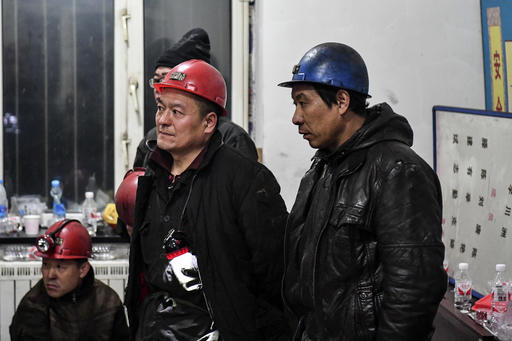 In this Wednesday, Nov. 30, 2016 photo released by Xinhua News Agency, rescuers and workers attend a briefing before conducting a search and rescue operation for workers trapped inside a coal mine in Qitaihe City, northeast China's Heilongjiang Province. The managers of an apparently unregistered coal mine in northeast China are under questioning as rescuers tried Thursday to reach workers trapped for a third day. (Wang Song/Xinhua via AP)