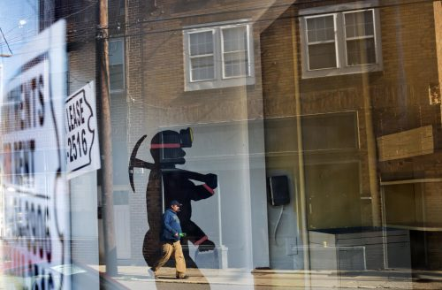 FILE - In this Oct. 17, 2014 file photo, a mural of a coal miner stands in an empty storefront as signs advertising vacant apartments and stores hang in the windows along the main business street in Cumberland, Ky. The world's biggest coal users - China, the United States and India - have boosted coal mining in 2017, in an abrupt departure from last year's record global decline for the heavily polluting fuel and a setback to efforts to rein in climate change emissions.(AP Photo/David Goldman, File)