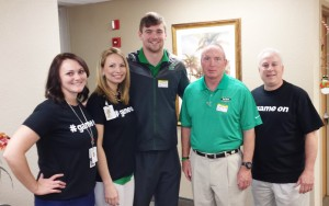 Hospital officials take a picture with Doc Holliday and the hospital's former little bundle of joy.