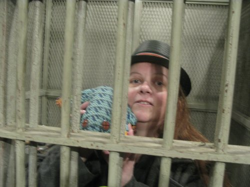 """Melanie in a cell with her """"Book of Mormon"""" frog"""