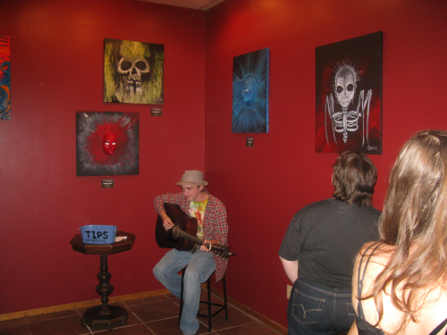 Christopher Carter providing the music, surrounded by his father, Johnny Carter's, paintings