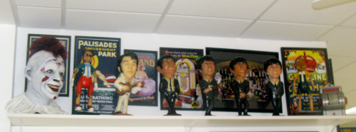 The tops of the walls, near the ceiling, sport shelves loaded with caracitures of famous stars