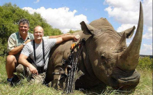"Palmer, with a White Rhino he killed. There are now four of these animals left in the world.This image comes up in Google Images when you search for ""A**hole Dentist."""