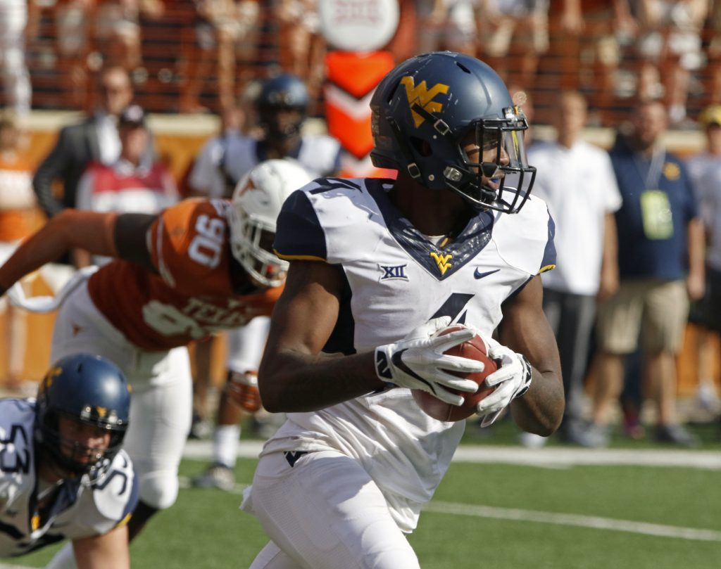 West Virginia running back Kennedy McKoy (4) runs the ball during the second half of an NCAA college football game against Texas, Saturday, Nov. 12, 2016, in Austin, Texas. West Virginia won 24-20. (AP Photo/Michael Thomas)