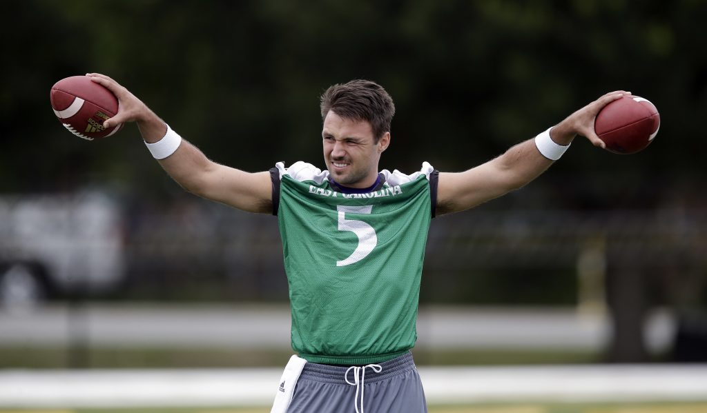 In this photo taken Friday, Aug. 4, 2017, East Carolina quarterback Garner Minshew warms up during the team's NCAA college football practice in Greenville, N.C. (AP Photo/Gerry Broome)