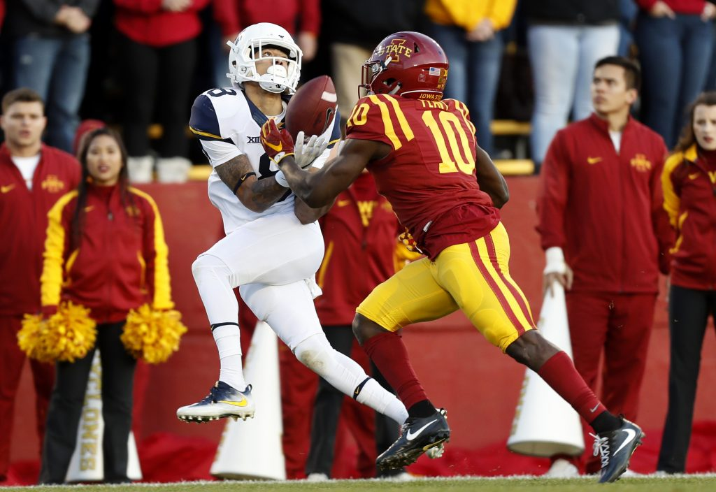 West Virginia wide receiver Marcus Simms, left, catches a 48-yard touchdown pass ahead of Iowa State defensive back Brian Peavy (10) during the first half of an NCAA college football game, Saturday, Nov. 26, 2016, in Ames, Iowa. (AP Photo/Charlie Neibergall)